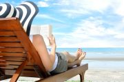 43648527 - young woman reading a book at the beach