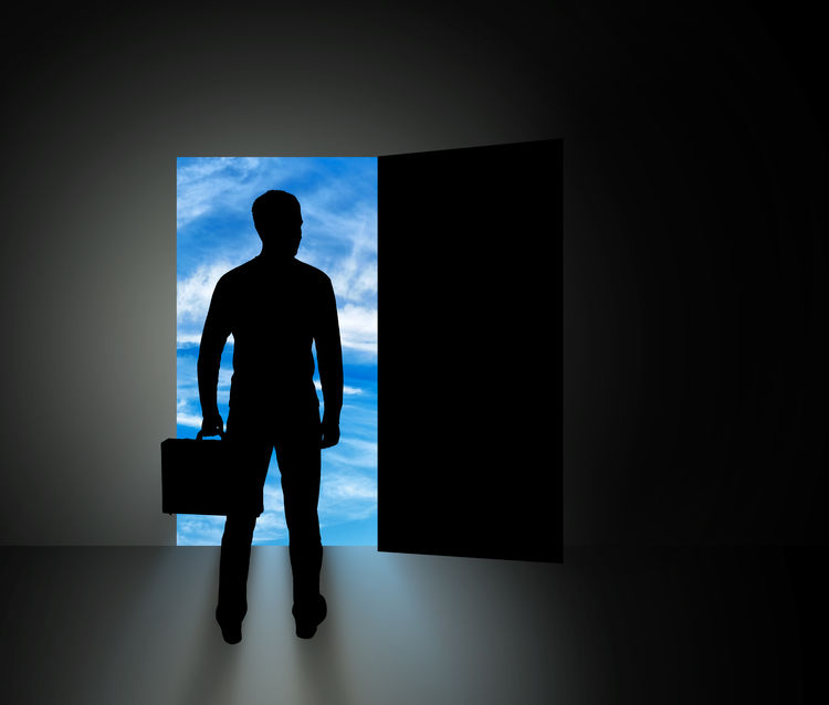 The concept of new business opportunities. Silhouette of businessman standing in front of open doors