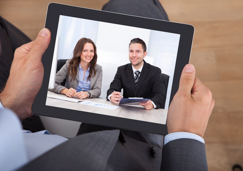 High angle view of businessman video conferencing with colleagues on digital tablet in office