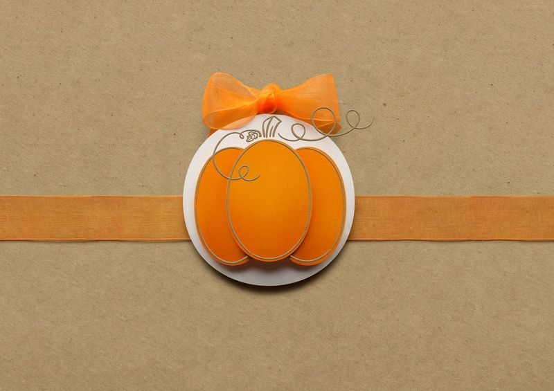 Creative thanksgiving day concept photo of pumpkin made of paper on brown background.