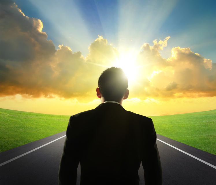 silhouette of business man look sunrise with asphalt road and green grass, business concept